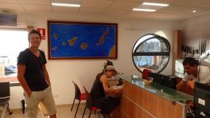 Terese ved at udfylde papirer på havnekontoret, Martin foran kort over canariske øer