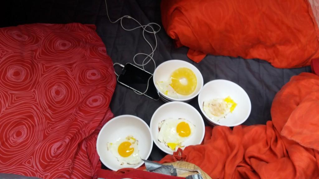 Frokost med spejlæg i dybe skåle bliver anrettet i køjen, da det krænger for meget på køkkenbordet!